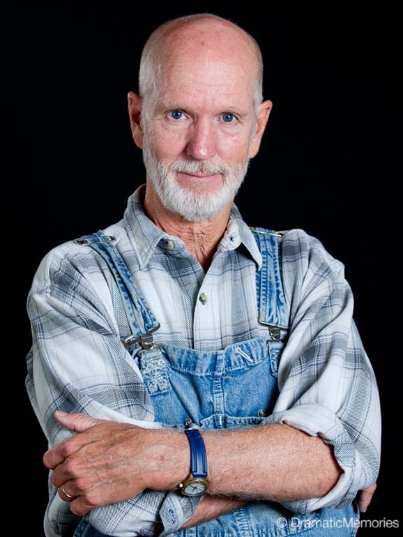 happy farmer standing in overalls and a plaid shirt