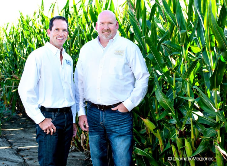 business owners standing near a corn field