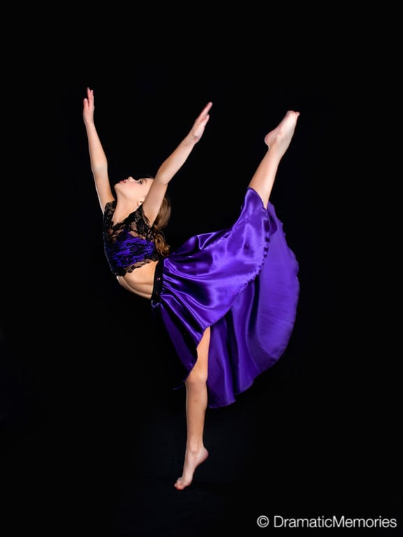 young girl dancer in a purple dress posing