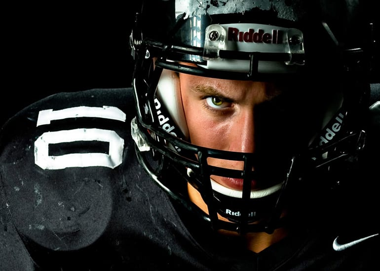 senior boy football player in dramatic lighting.