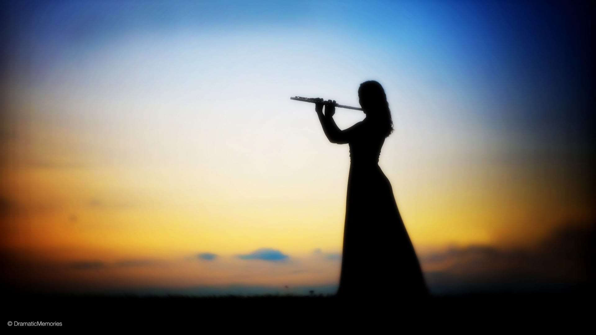 silhouette of a musician playing her flute at sunset