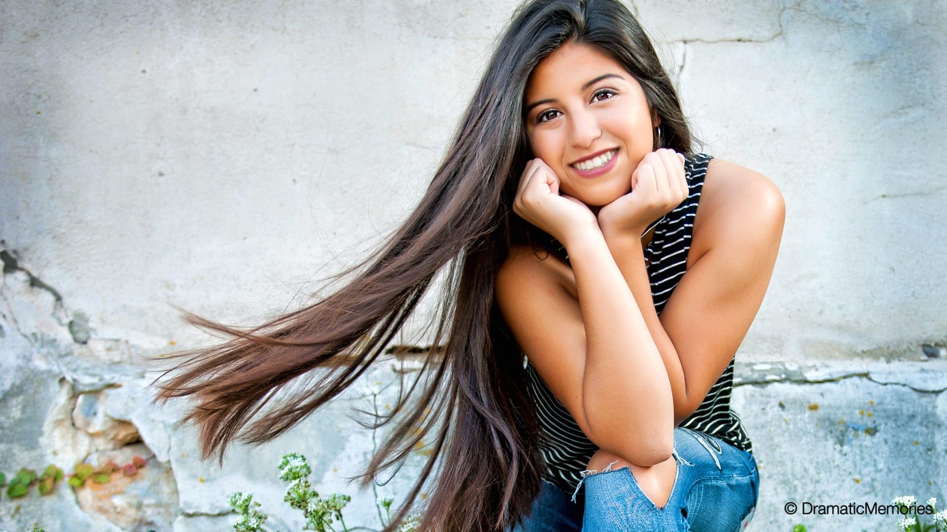 latino senior girl sitting outside near an old wall