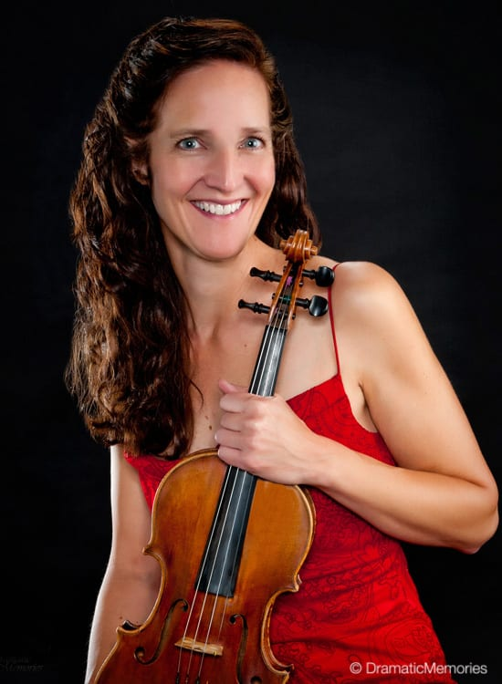 smiling musician in a red dress holding her instrument