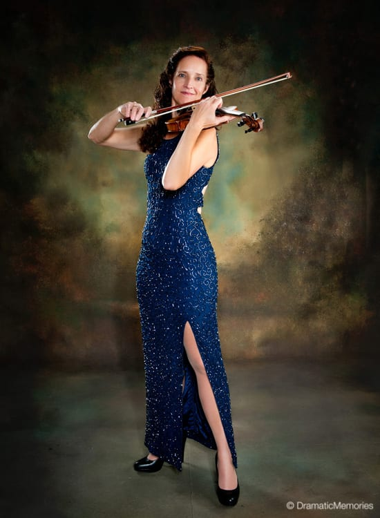 violinist playing her violin in a formal blue dress